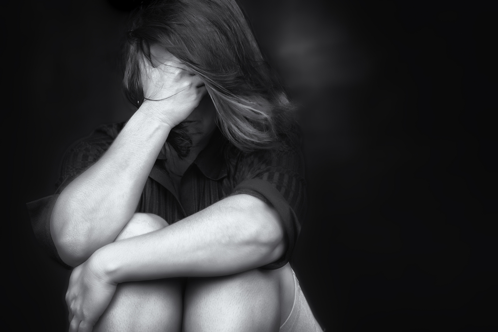 Black and white image of a young woman crying and covering her face useful to illustrate stress, depression or domestic violence